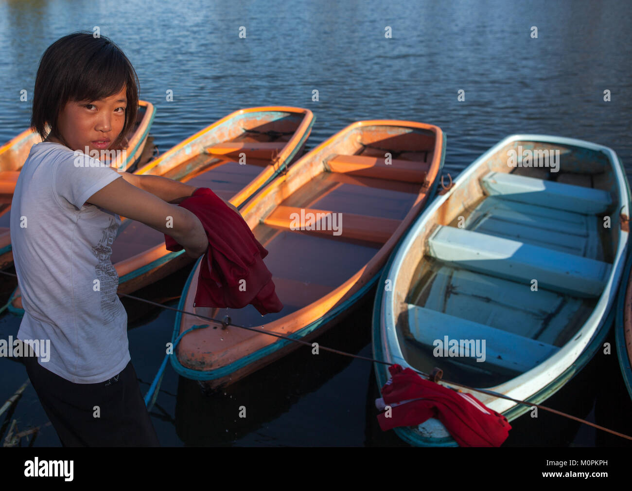North Korean girl washing her clothes in the lake of the Songdowon international children's camp, Kangwon Province, Stock Photo