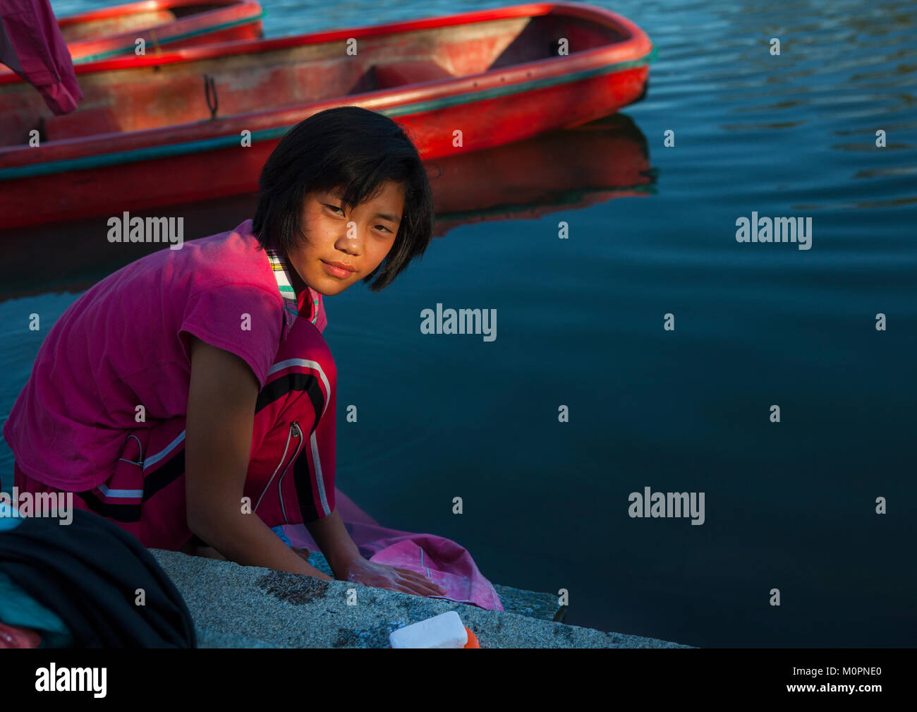 North Korean girl washing her clothes in the lake of the Songdowon international children's camp, Kangwon Province, - Stock Image