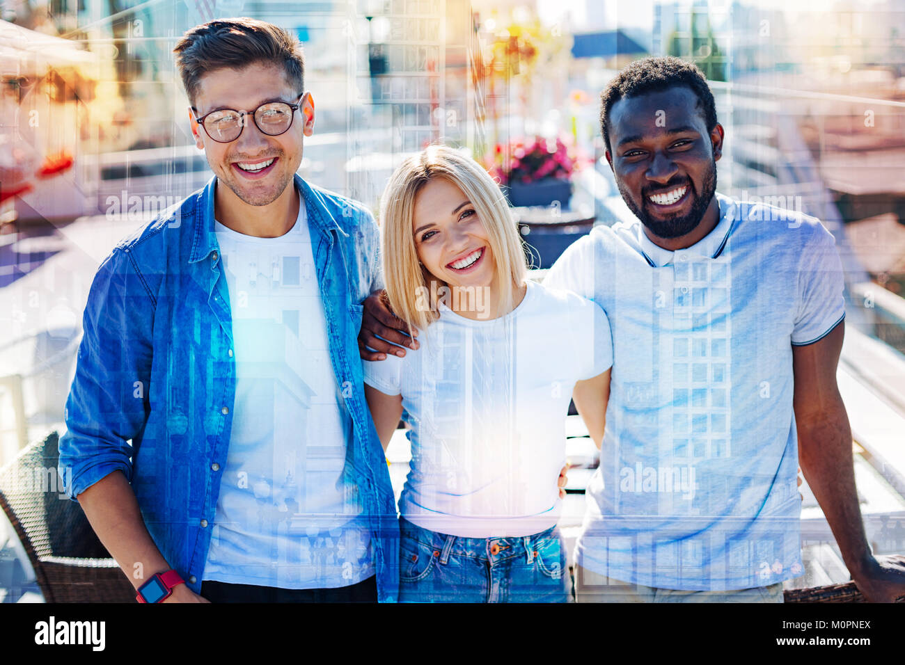 Happy colleagues smiling and standing together - Stock Image