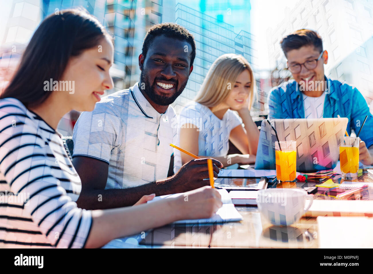 Joyful afro-american working with his colleagues - Stock Image