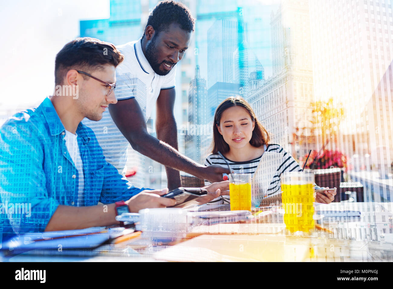 Happy afro-american man discussing work with his team - Stock Image