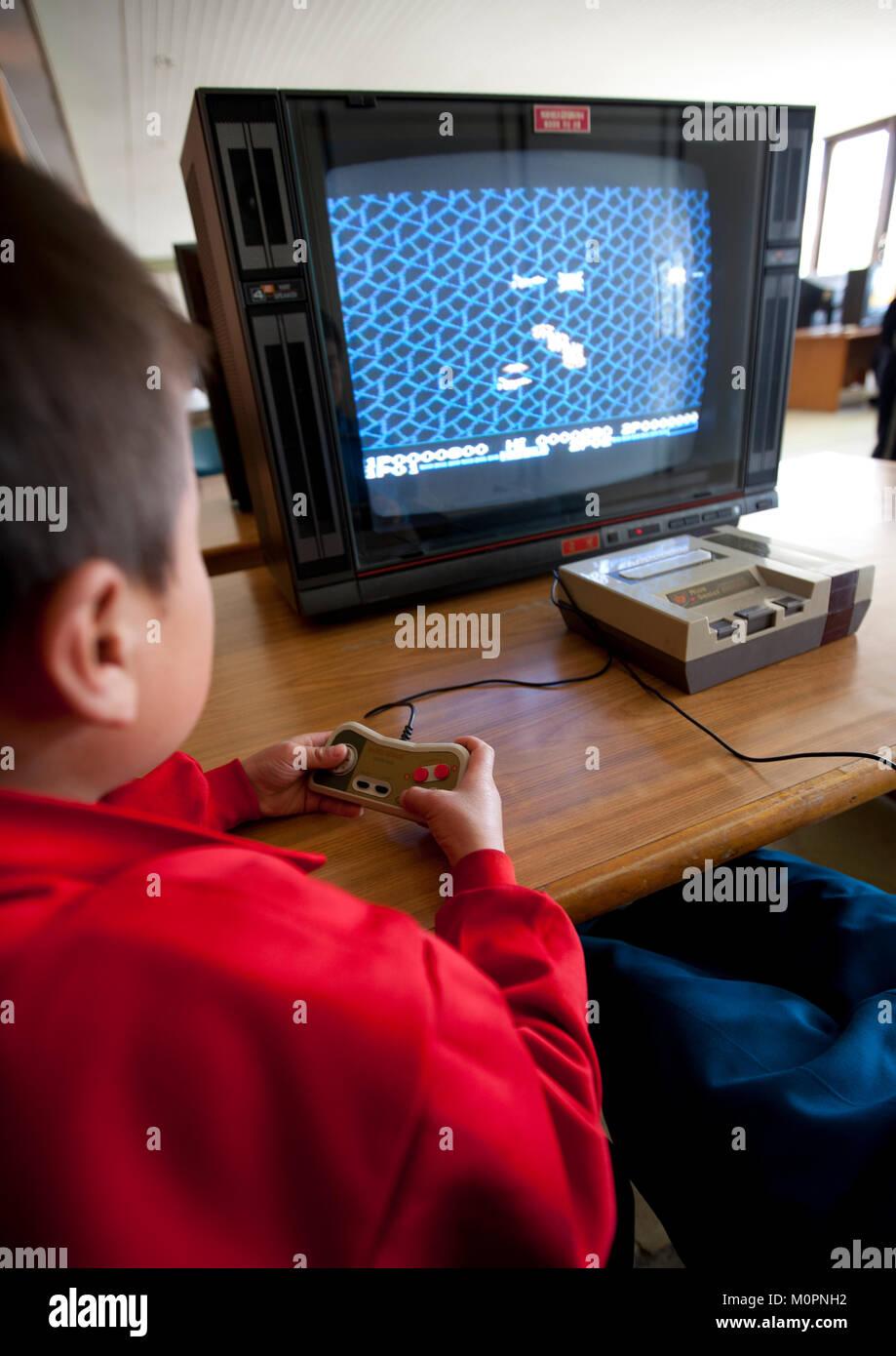 North Korean child playing video games in Songdowon international children's camp, Kangwon Province, Wonsan, - Stock Image