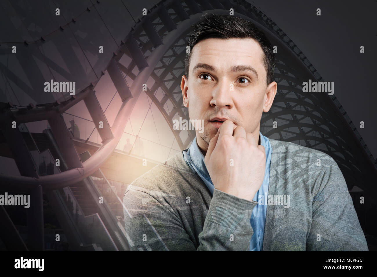 Concentrated millennial guy generating ideas - Stock Image