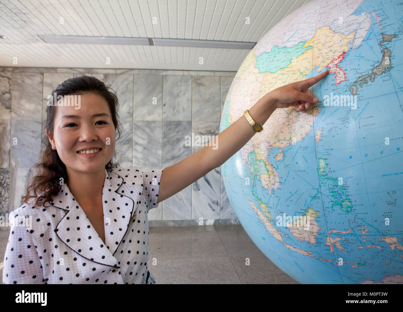 Female guide showing North Korea on a globe at Songdowon international children's camp, Kangwon Province, Wonsan, - Stock Image