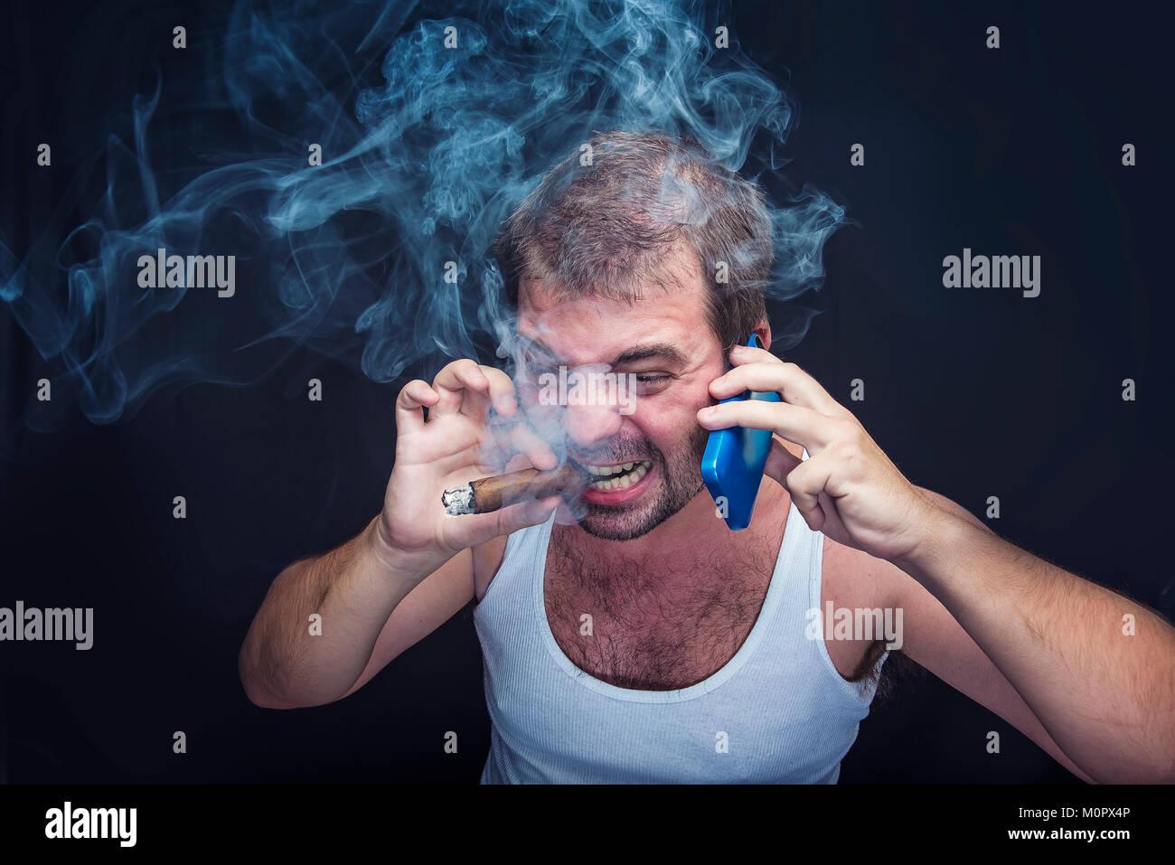 Rude smoking man yelling at his cell phone - Stock Image