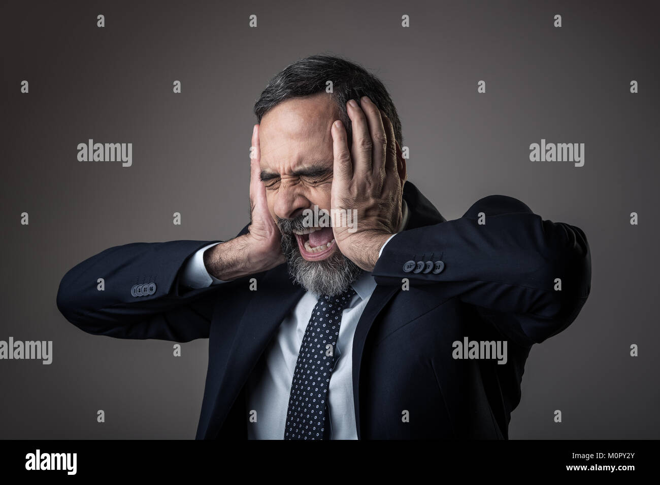 Angry business man with a terrible headache - Stock Image