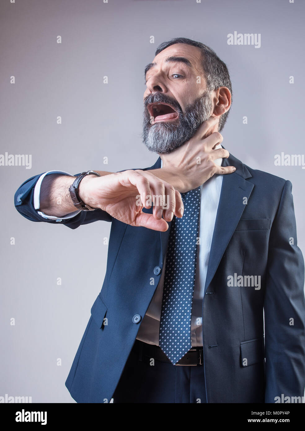 Wristwatch choking a senior business man - Stock Image