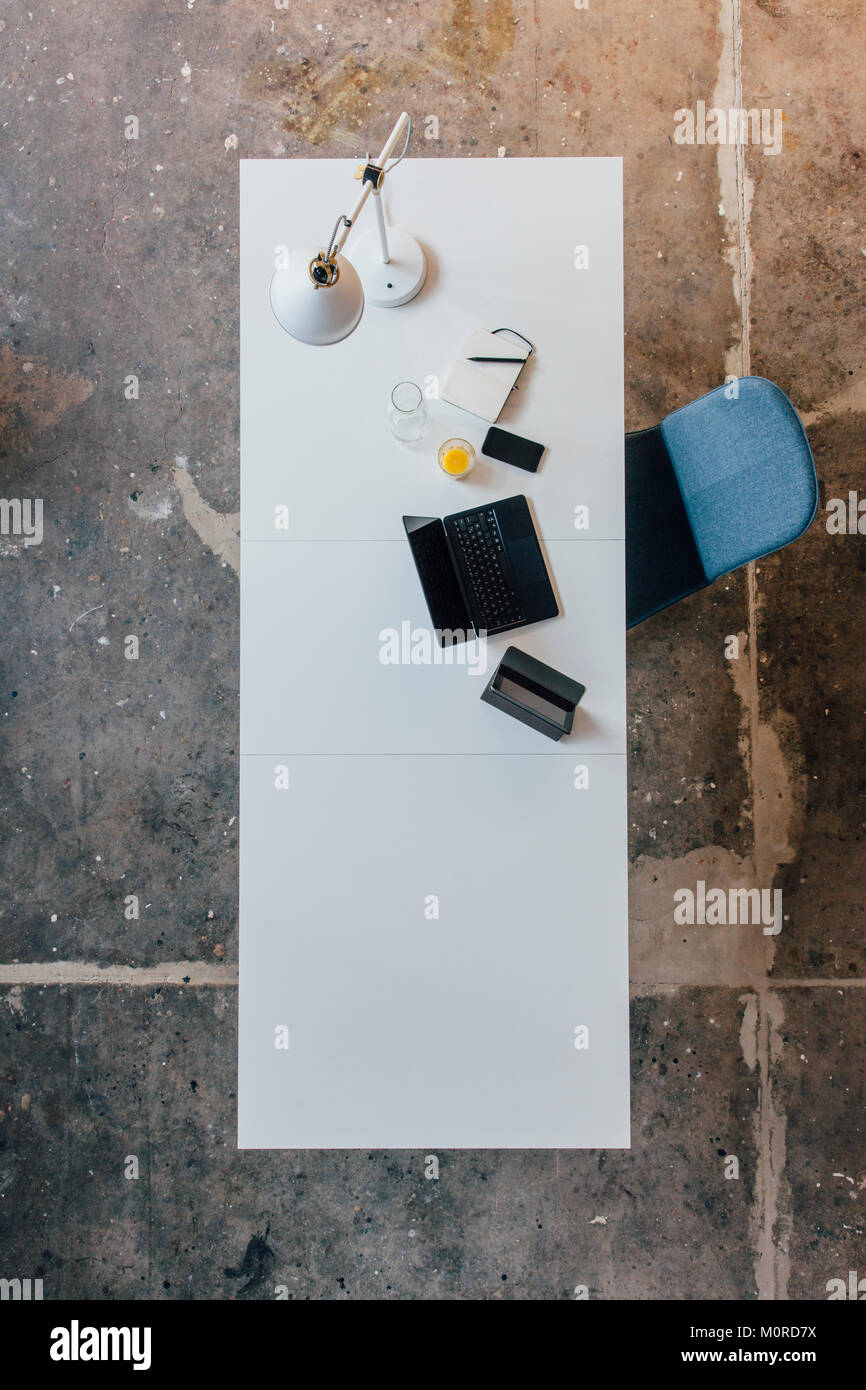 Desk seen from above, tablet, smartphone, laptop, orange juice and notebook Stock Photo