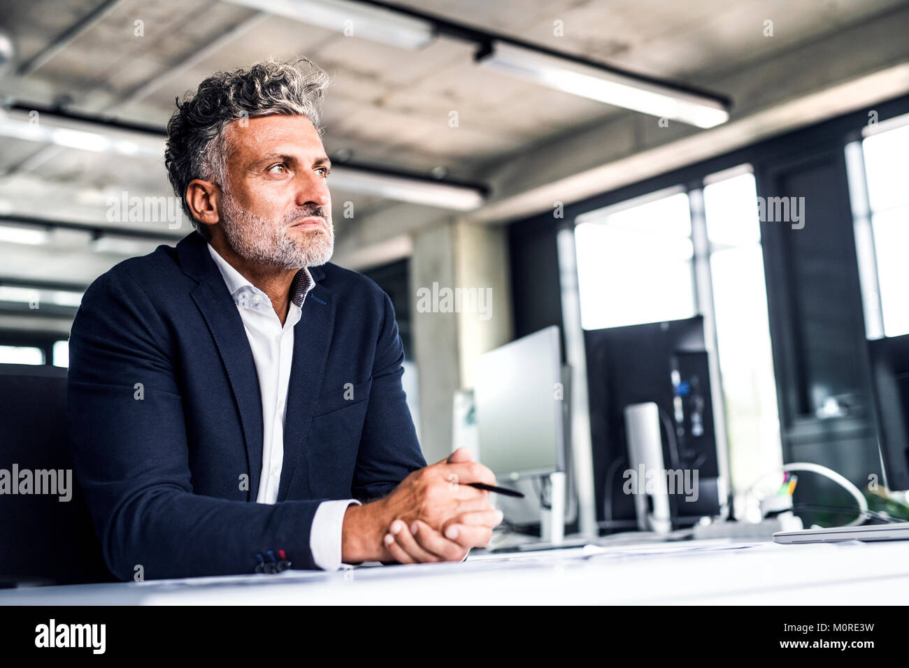 Mature businessman in office thinking - Stock Image