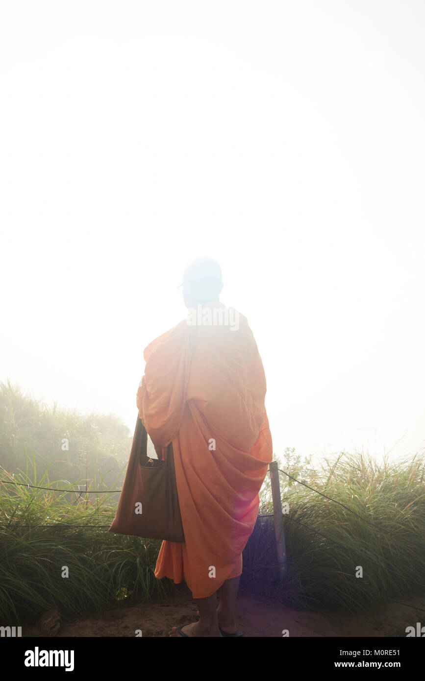Unrecognizable buddhist monk praying with orange tunic over the mountains. - Stock Image