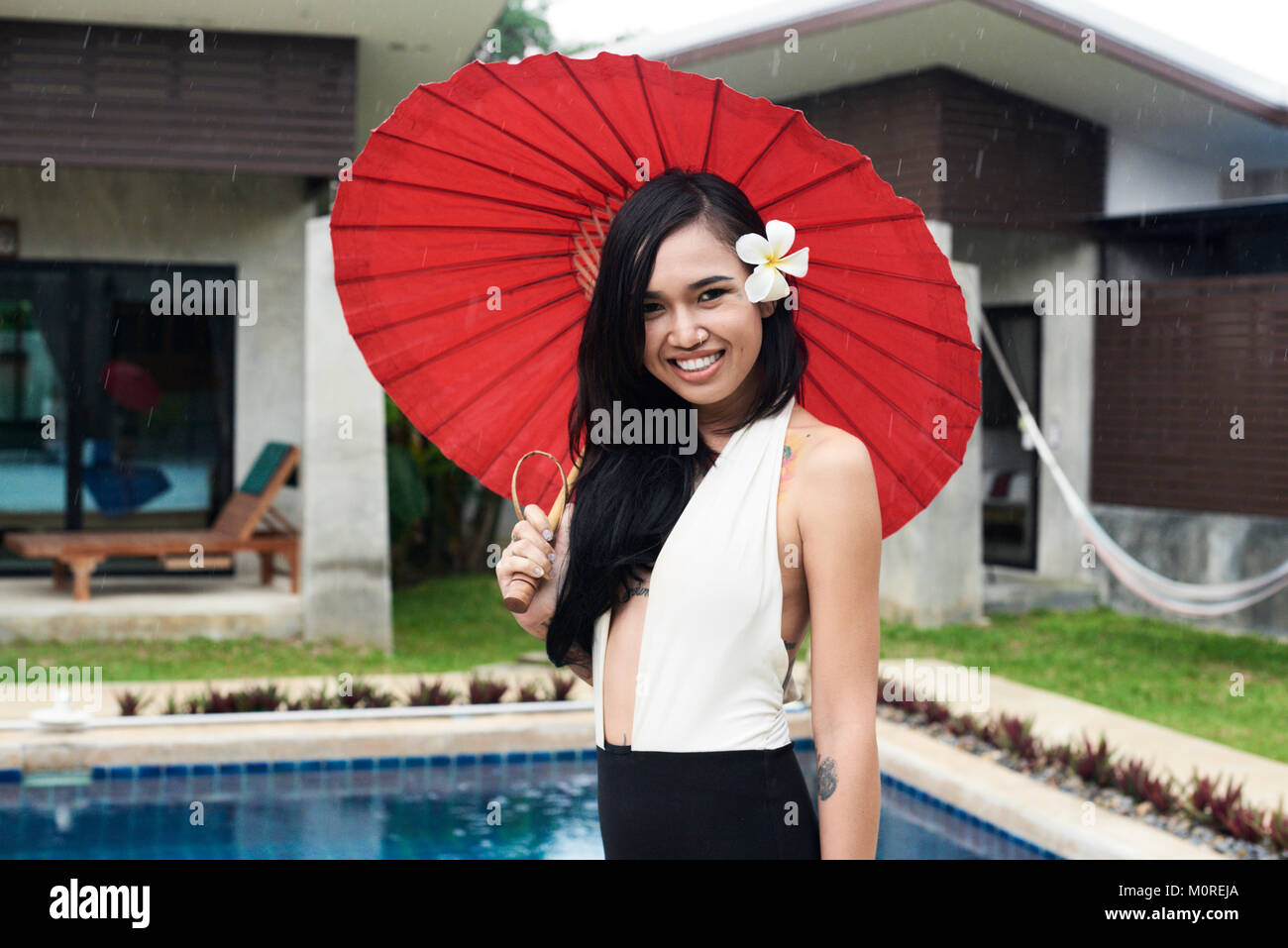 5e45d6e66c2dd Pretty asian brunette millennial holding a red tradtional umbrella next to  the swimming pool smiling at