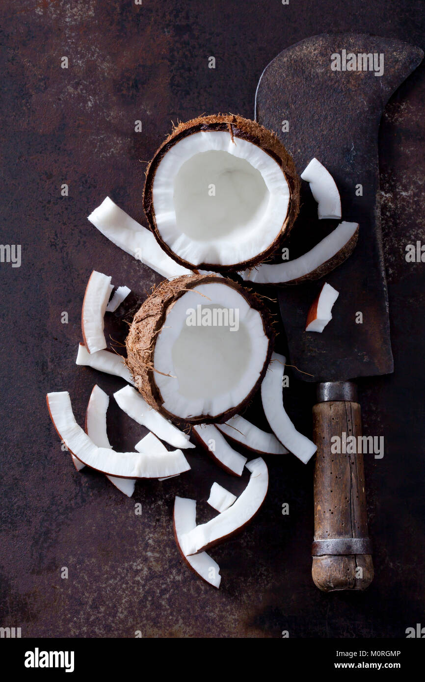 Opened coconut, cocontu pieces and an old cleaver - Stock Image
