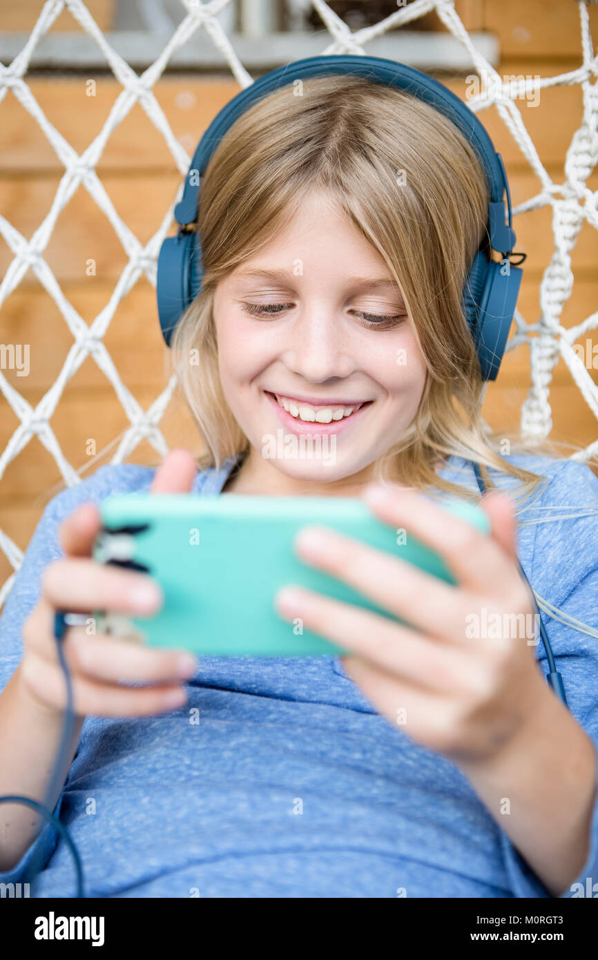 Portrait of happy girl with headphones and smartphone in a hanging chair - Stock Image