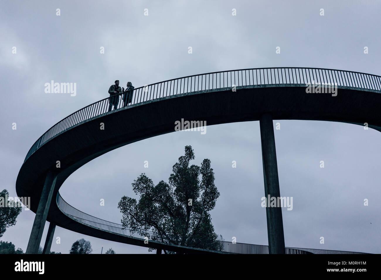 Two businessmen standing on dark bridge, having a meeting - Stock Image