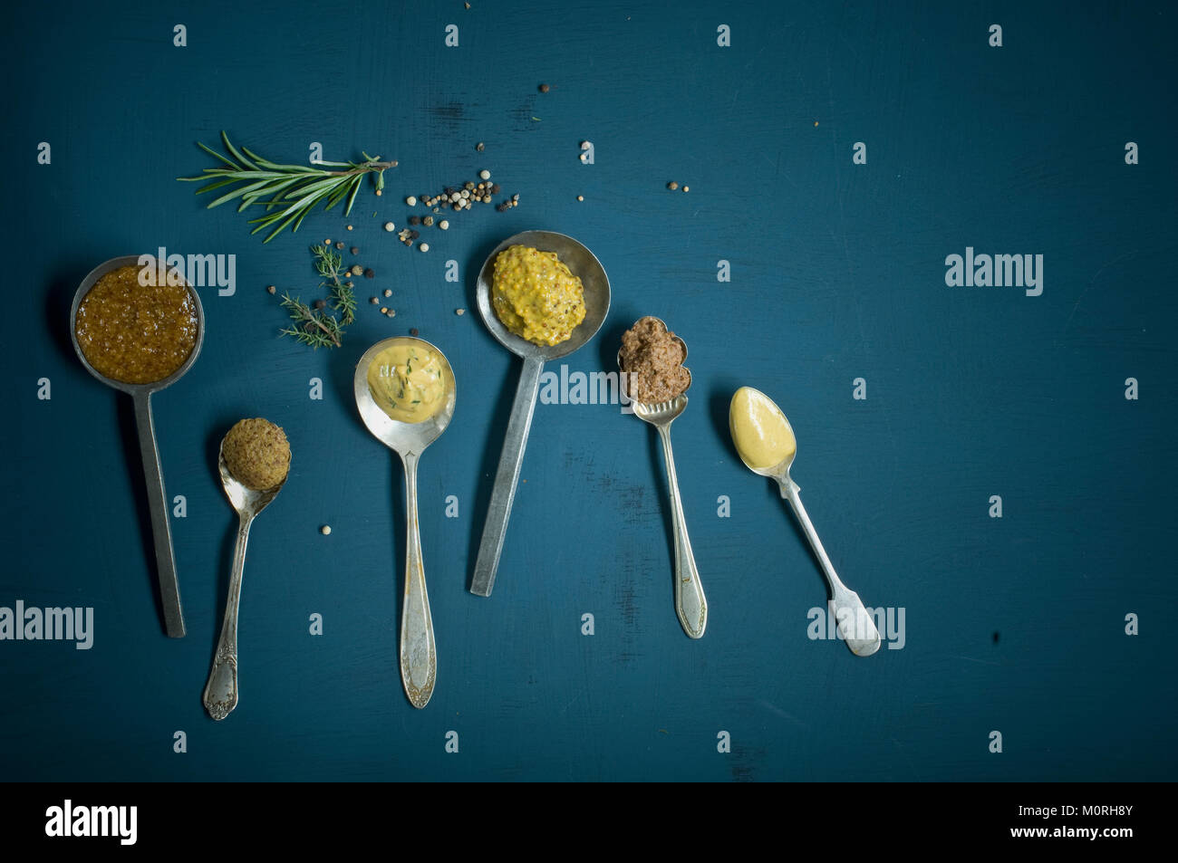 Homemade mustard, different sorts on spoon, honey mustard, sweet mustard, red wine mustard, herb mustard, grainy - Stock Image