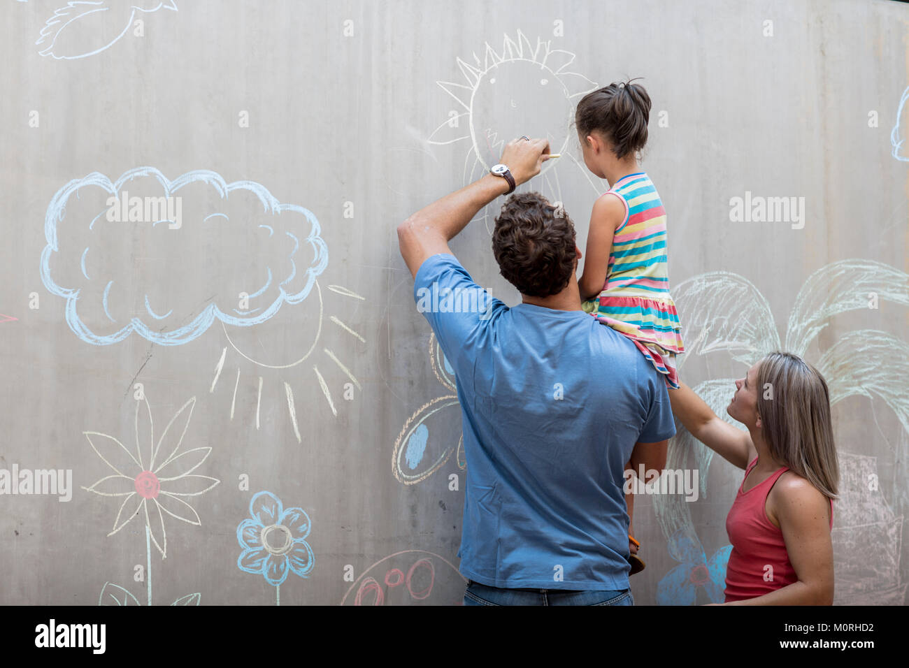 Family drawing colourful pictures with chalk on a concrete wall - Stock Image