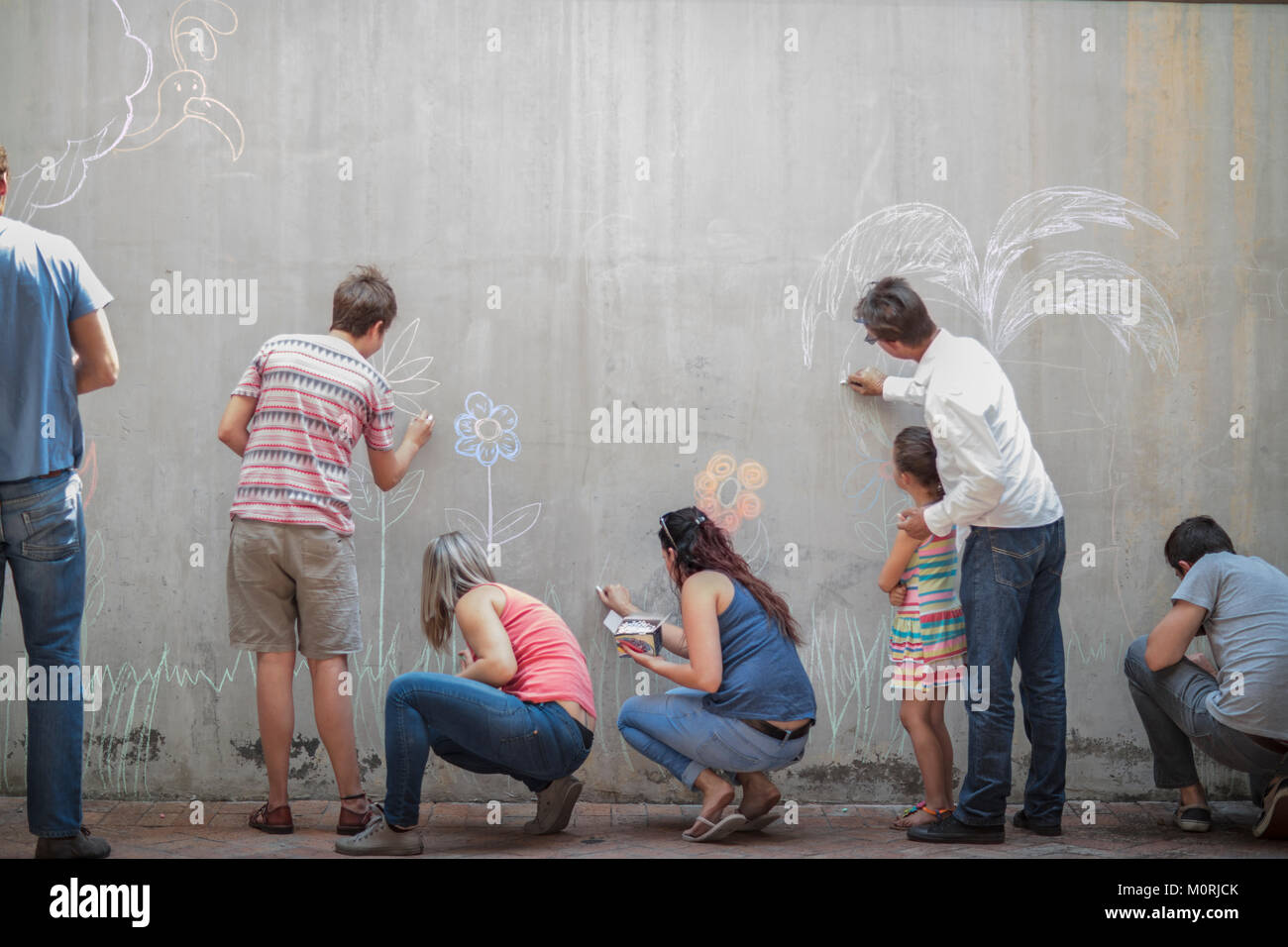 People drawing colourful pictures with chalk on a concrete wall - Stock Image