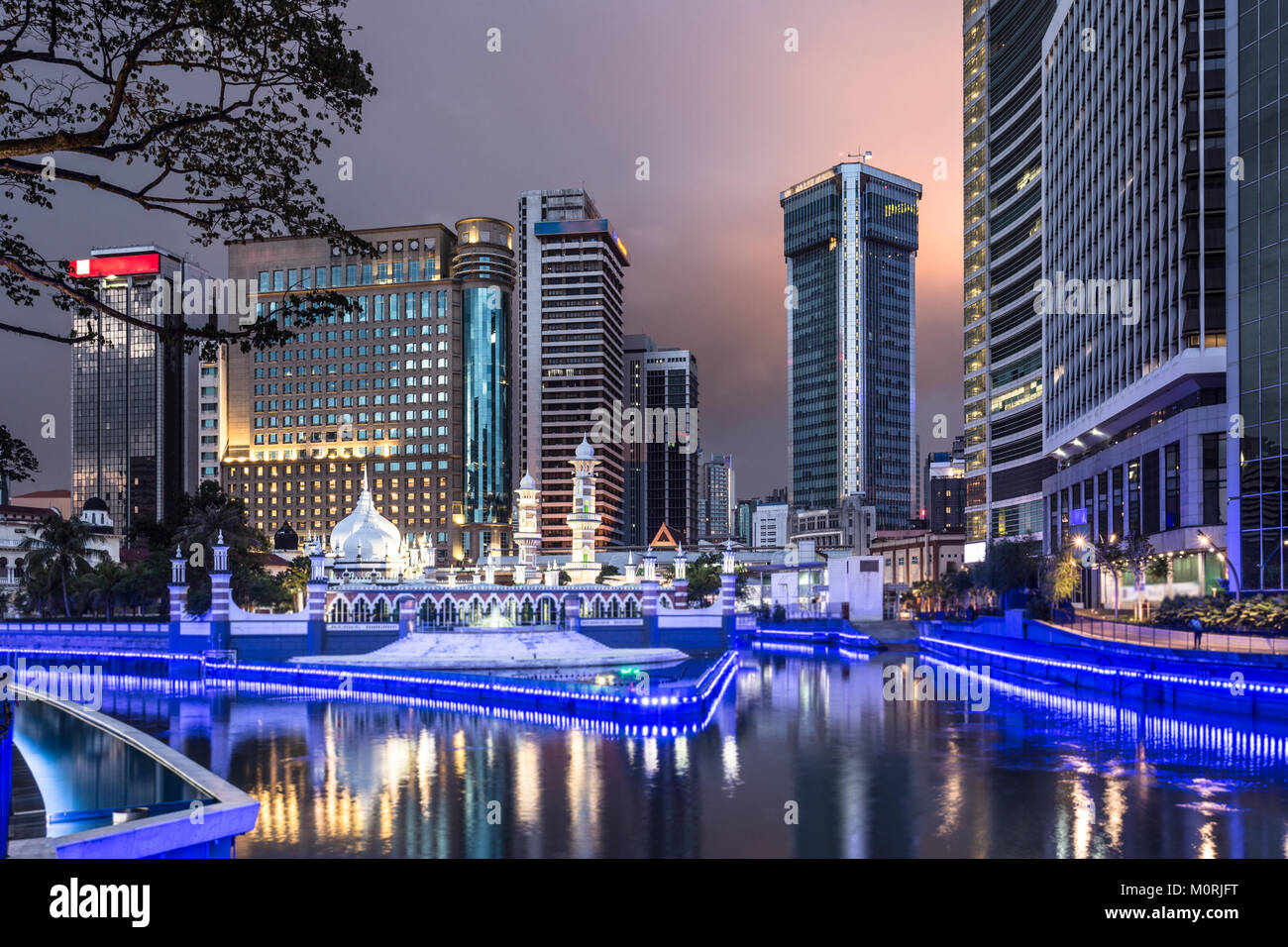 Office buildings reflect in the water of the Klang river in front of the Jamek mosque (masjid) in the heart of Kuala - Stock Image