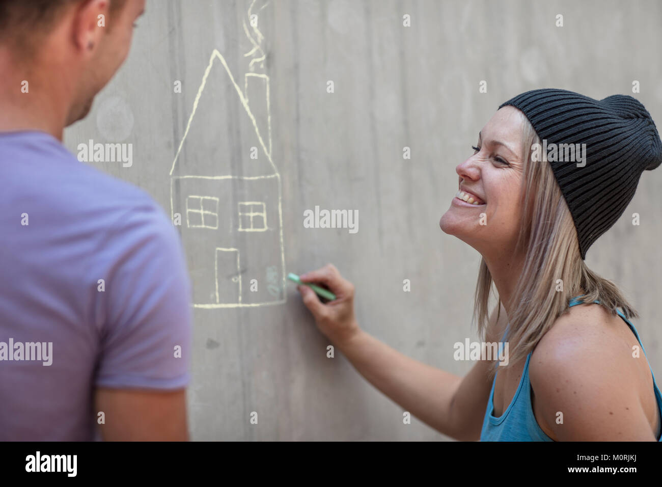 Man and woman drawing a house with chalk on concrete wall - Stock Image