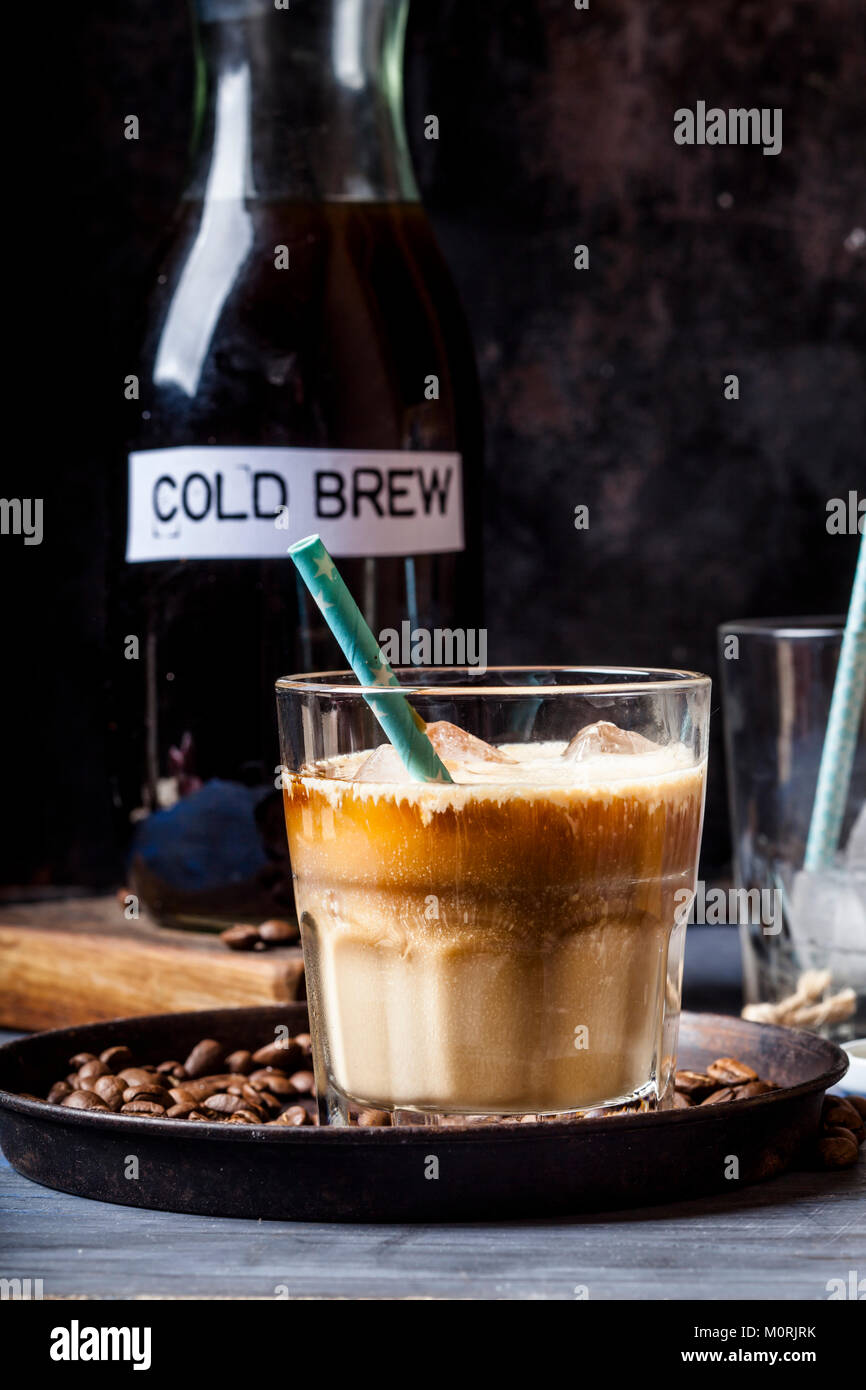 Cold brew coffee with ice cubes and coffee creamer - Stock Image