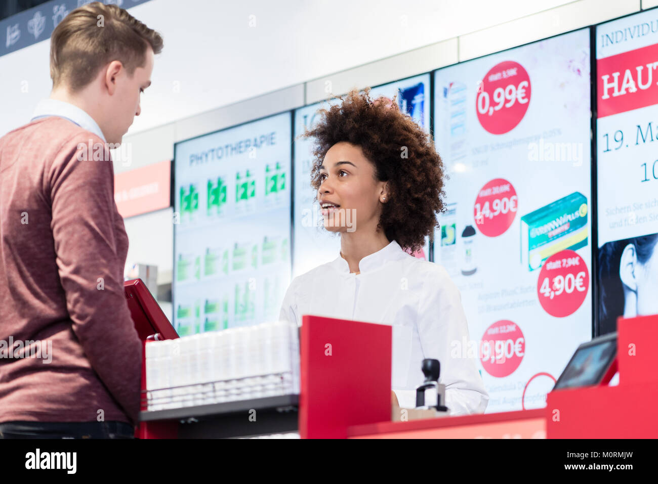pharmacist answering question of a young customer in a modern dr - Stock Image