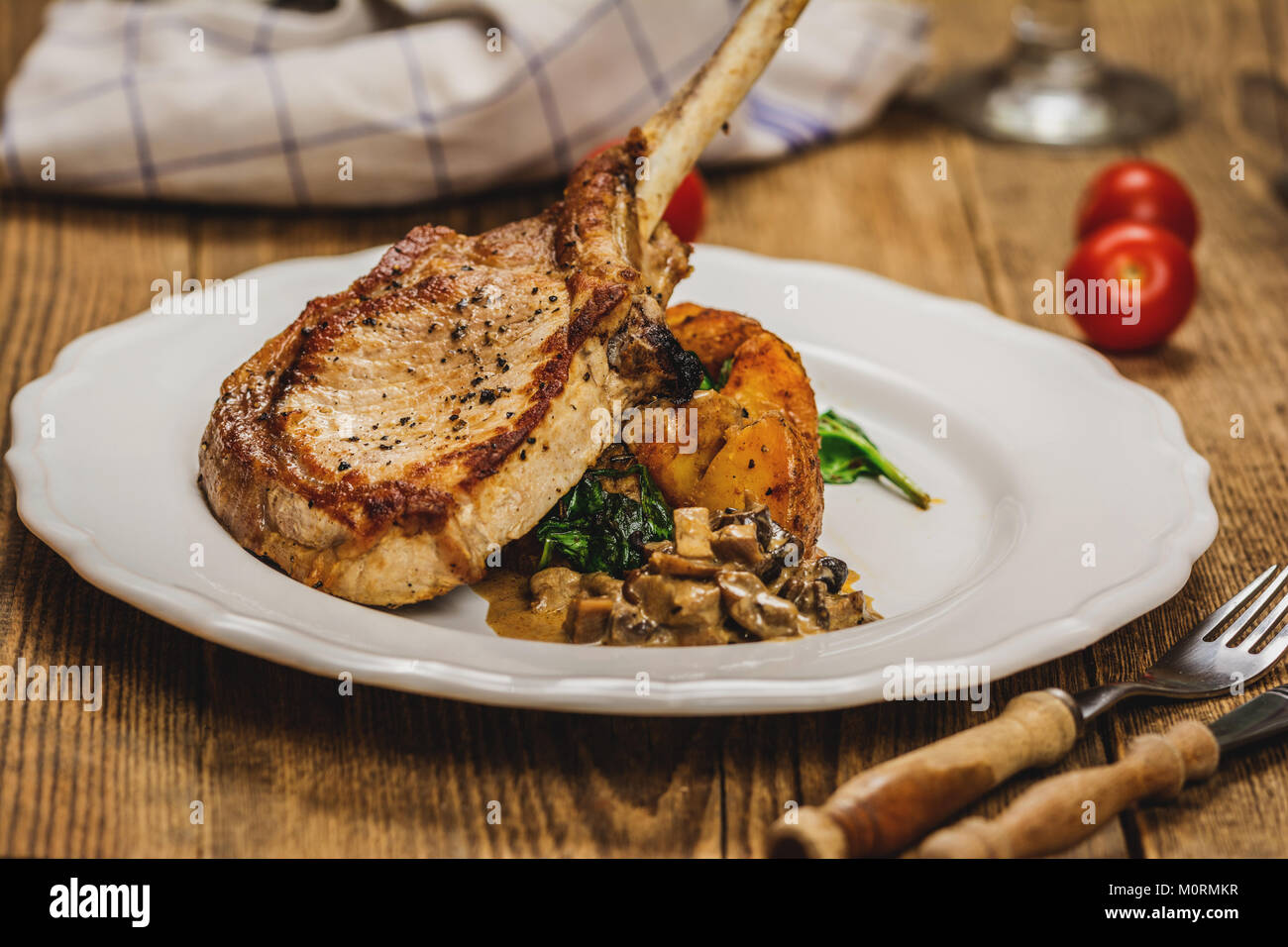Baked pork chops or cutlet with mushroom sauce and potatoes with spinach - Stock Image