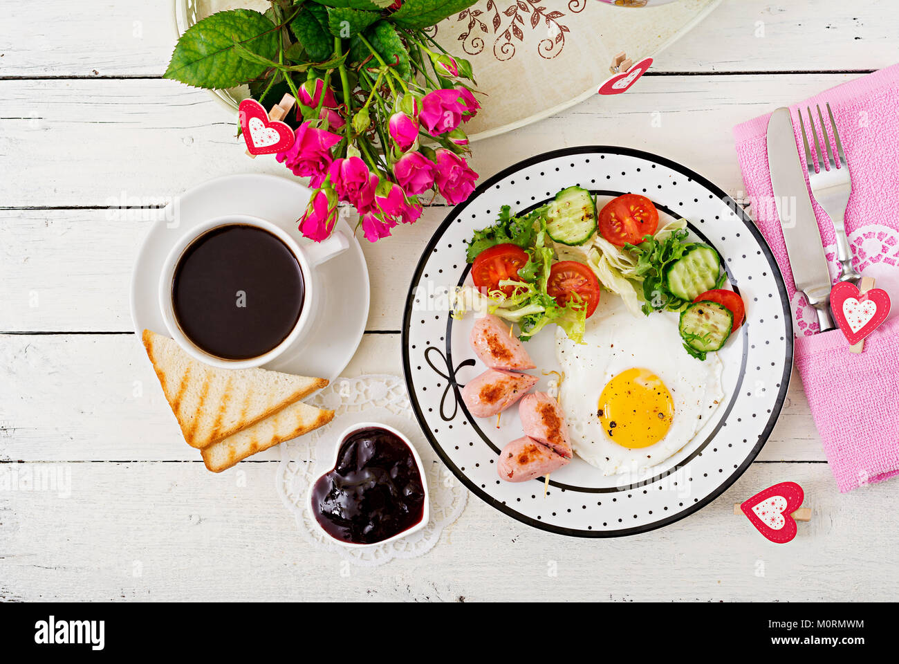 Breakfast on Valentine's Day - fried egg in the shape of a heart, toasts, sausage and fresh vegetables. Cup - Stock Image