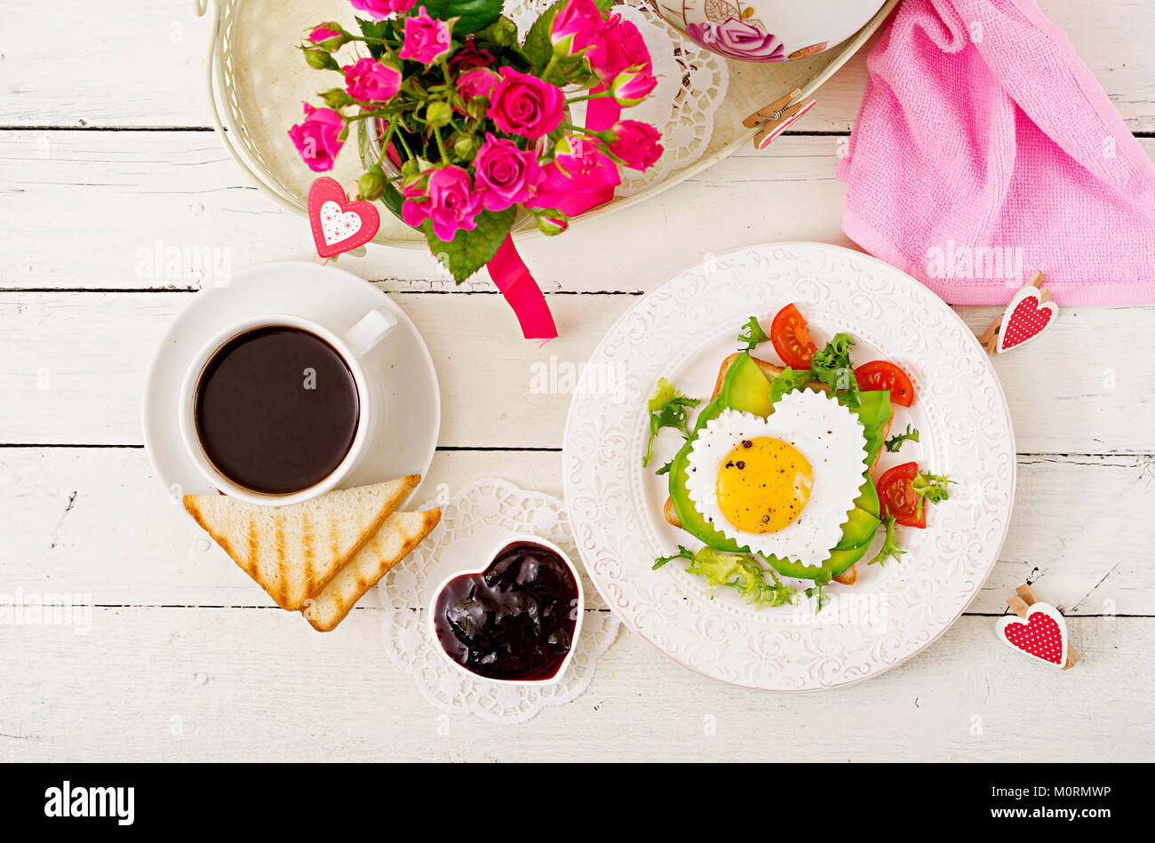 Breakfast on Valentine's Day - sandwich of fried egg in the shape of a heart, avocado and fresh vegetables. - Stock Image