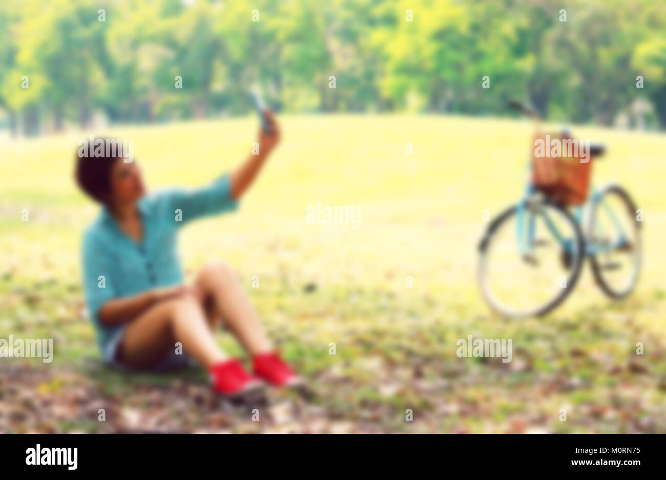 Beautiful young woman using a moblie phone in a park. Portrait, Style image blur Stock Photo