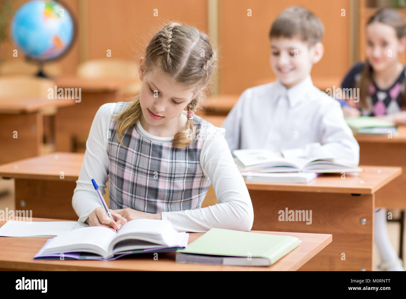Education, school, learning and children concept - group of school kids with pens and textbooks writing test in Stock Photo