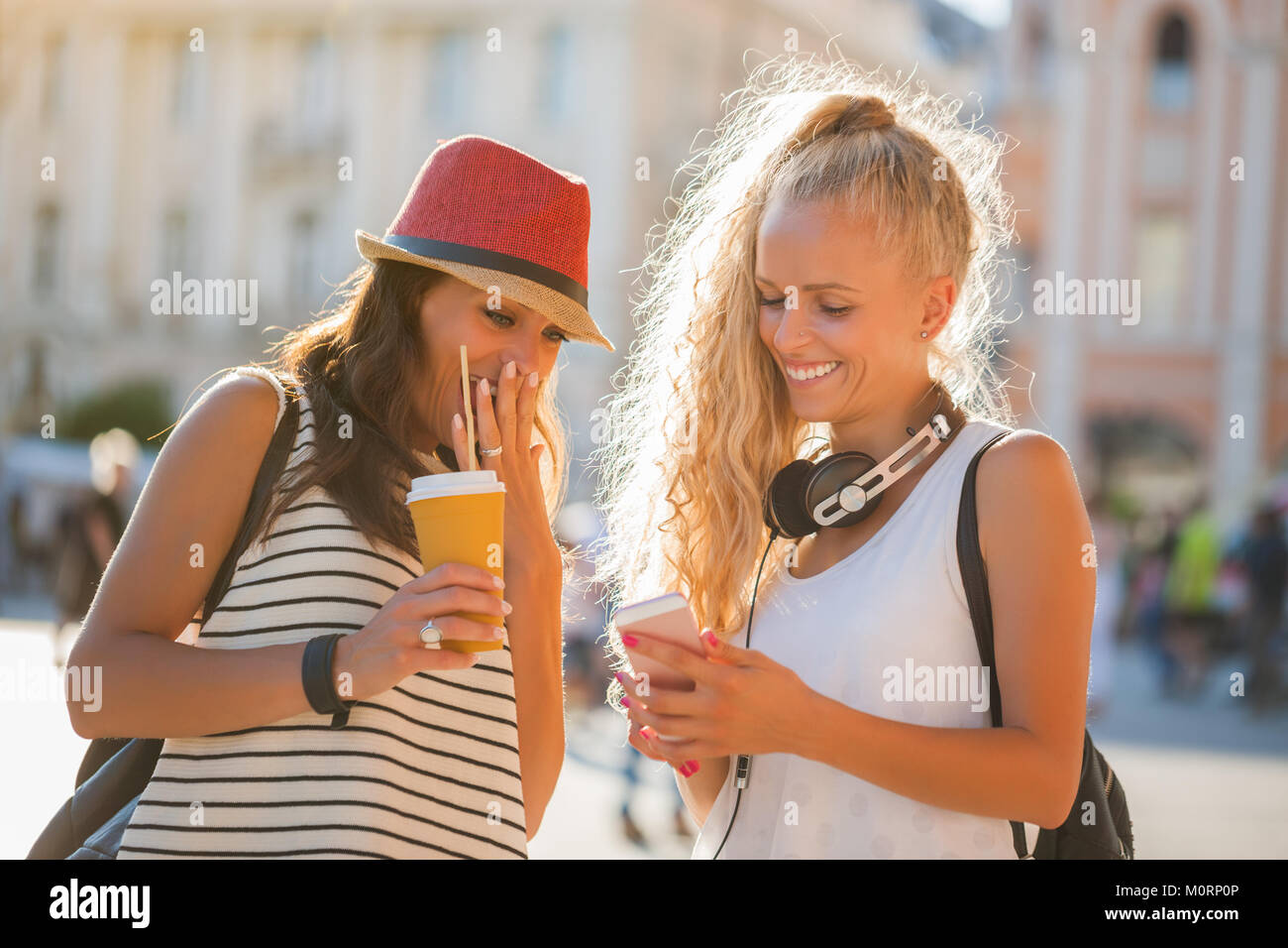 Two happy women are having nice time together in the city. - Stock Image