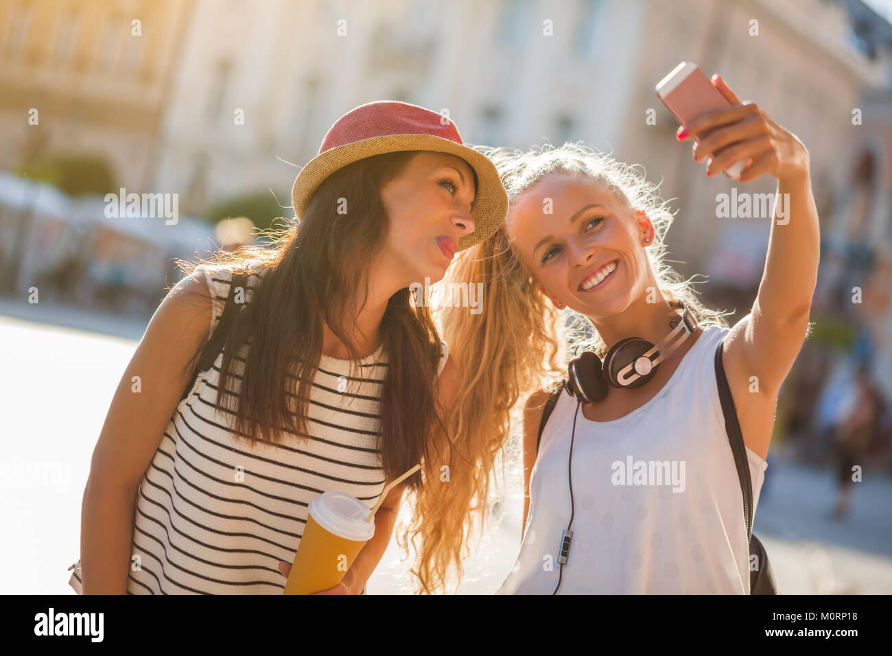 Two happy women are having nice time together in the city. They are taking selfie. - Stock Image