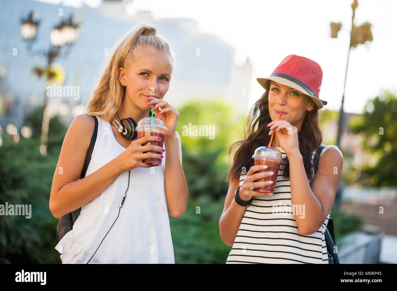 Two happy women are having nice time together in the city. They are drinking smoothie. - Stock Image