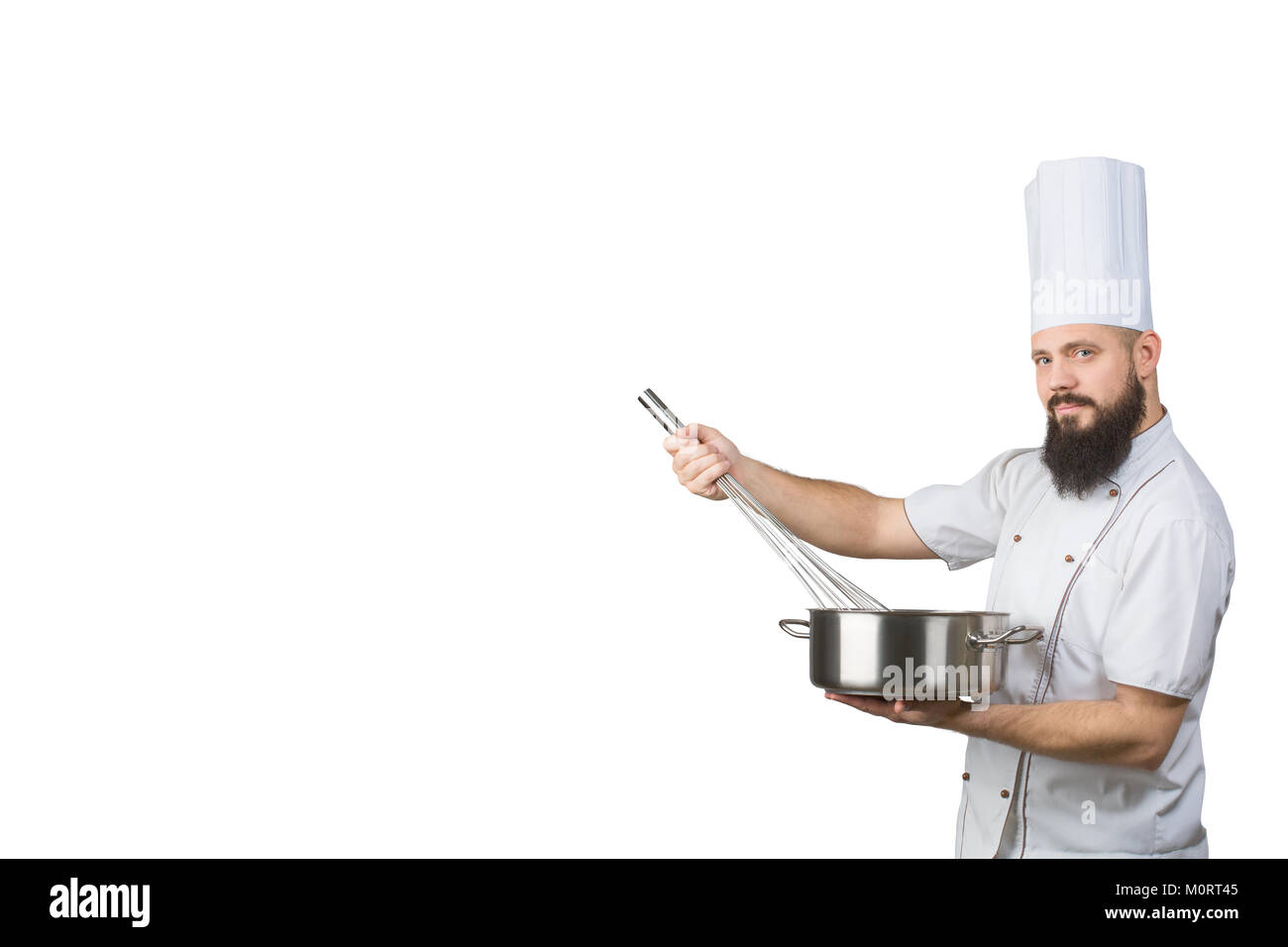 bearded cook whisking smth in a saucepan and looking to the camera isolated on a white background. Space for text - Stock Image