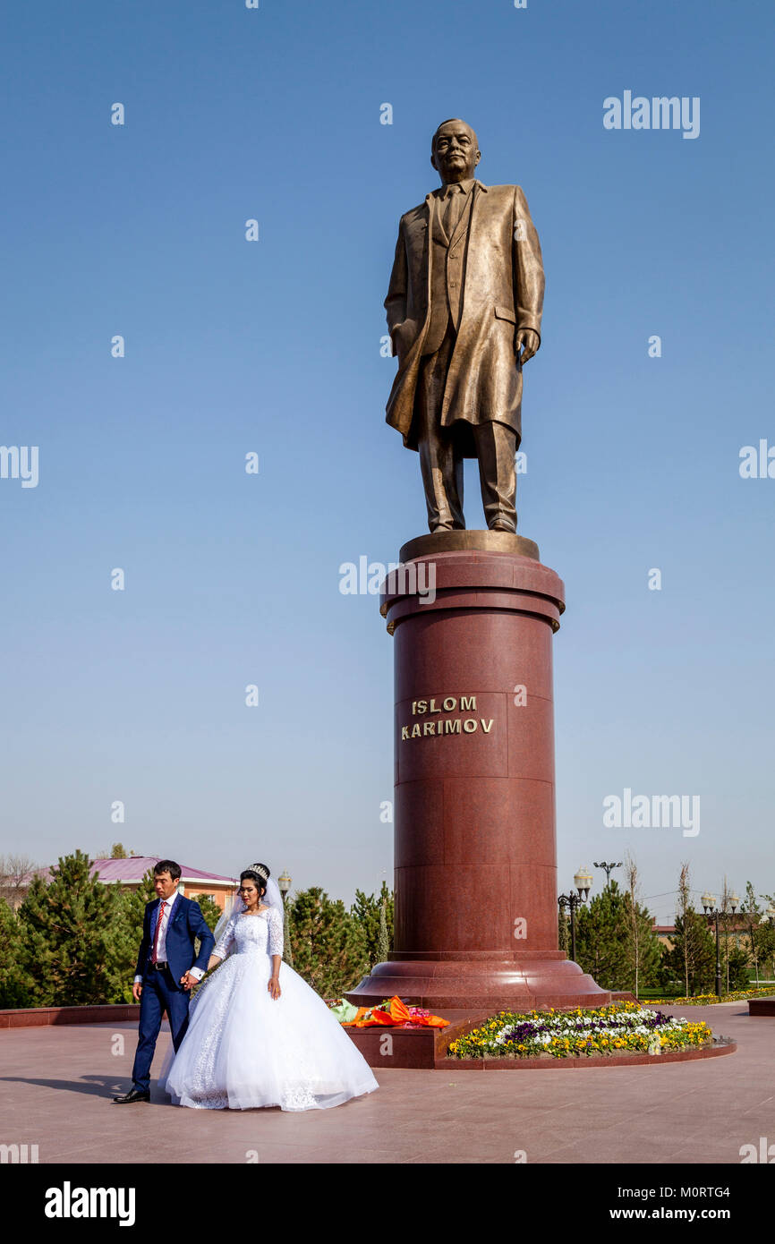 A 'Just Married' Couple Pose For A Wedding Photo Next To The Statue Of The Revered Former President Islam Karimov, - Stock Image