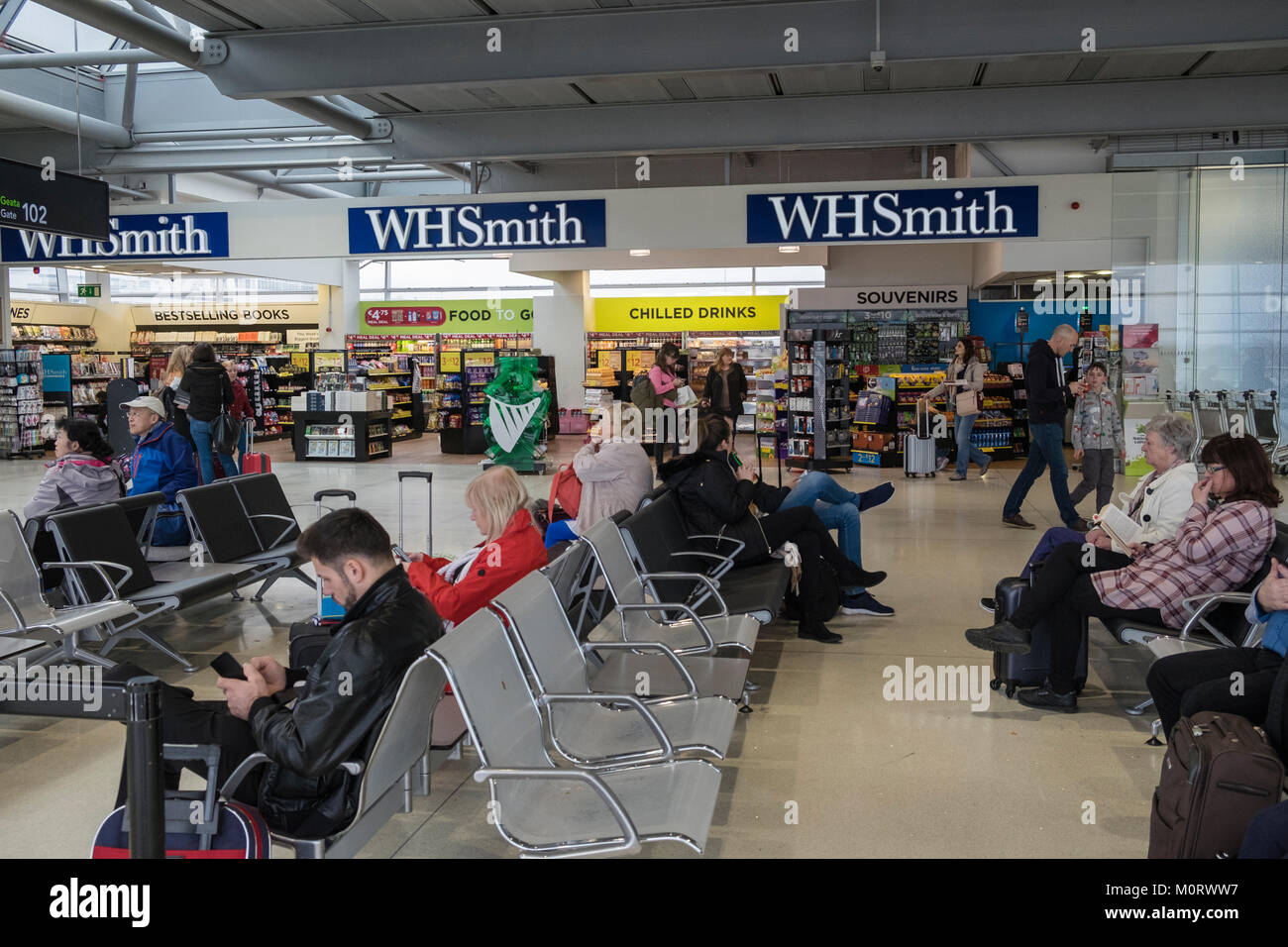 W H Smith shop in departures lounge next to departure gate with passenger seating area, Dublin airport, Ireland - Stock Image