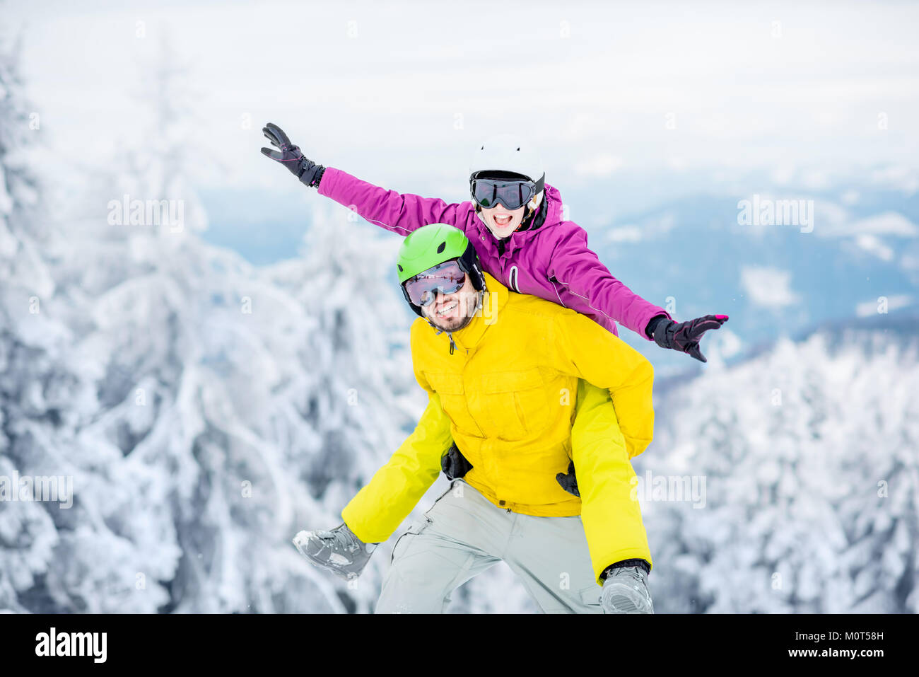 Couple in sports clothes during the winter vacation on the mountains - Stock Image