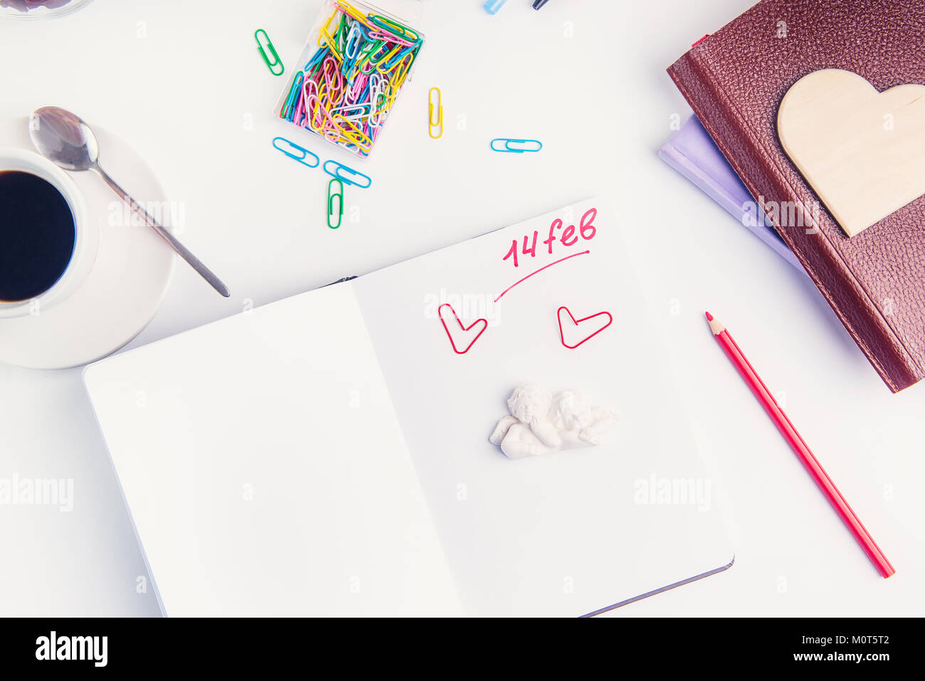 Red handwriting number fourteen febuary, Valentine's day text and angels stauette on personal organizer on the working place. Valentine's Day planning concept. Selective focus. Stock Photo