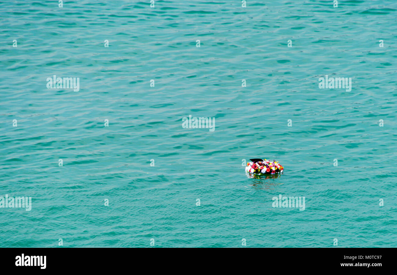 A wreath of flowers is dropped into the sea during a ceremony during Remembrance Day / Veterans Day / Armistice - Stock Image