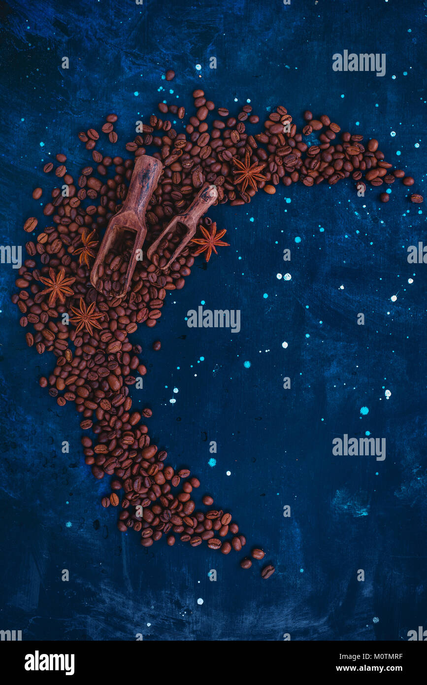 Wooden scoops for coffee beans in a vignette with copy space on a dark background. Ingredients for making coffee Stock Photo