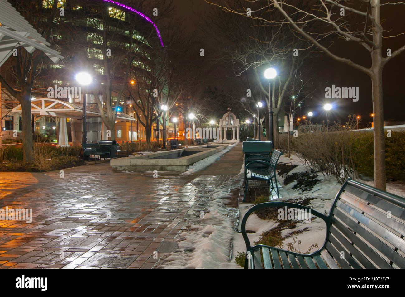 Park bench in the snow in Dayton, Ohio at night with city lights in the background. - Stock Image