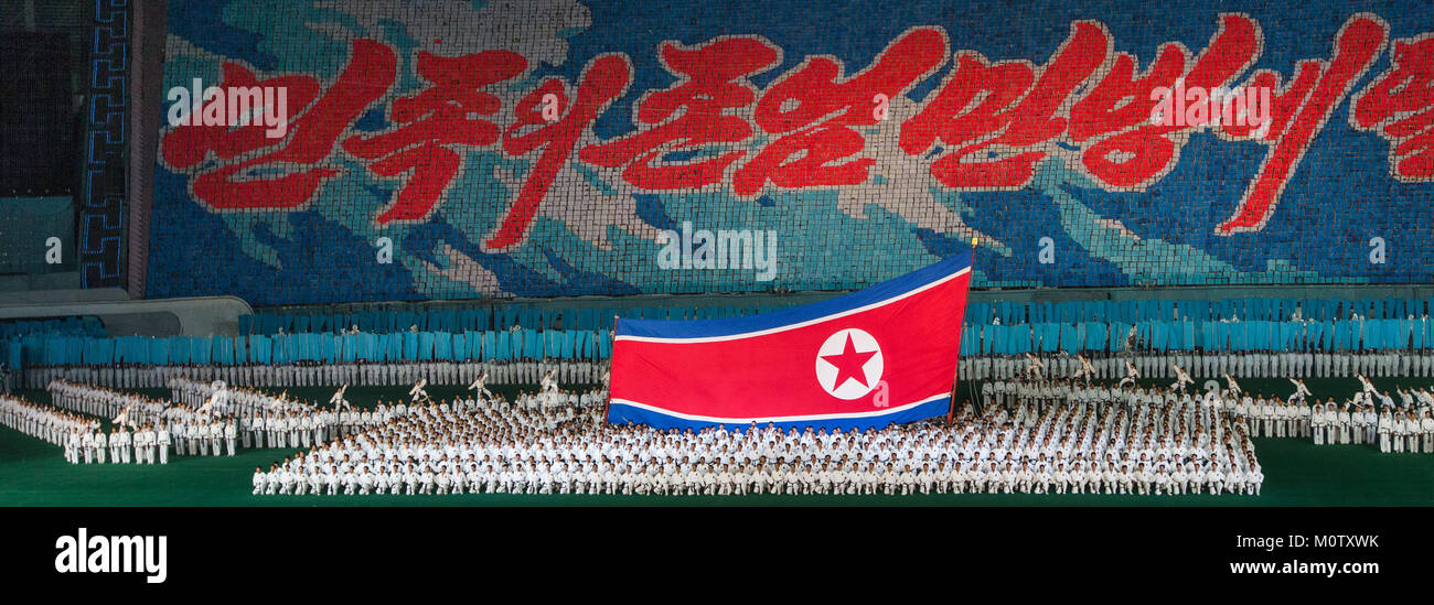 North Korean taekwondo team in front of a giant flag during the Arirang mass games in may day stadium, Pyongan Province, - Stock Image