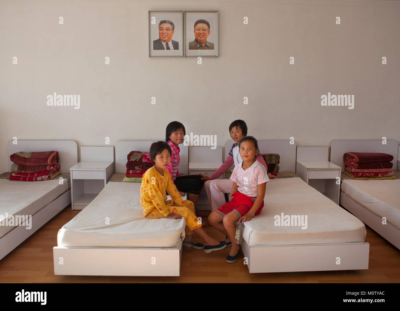 North Korean girls in a room under the official portraits of the Dear Leaders in Songdowon international children's Stock Photo