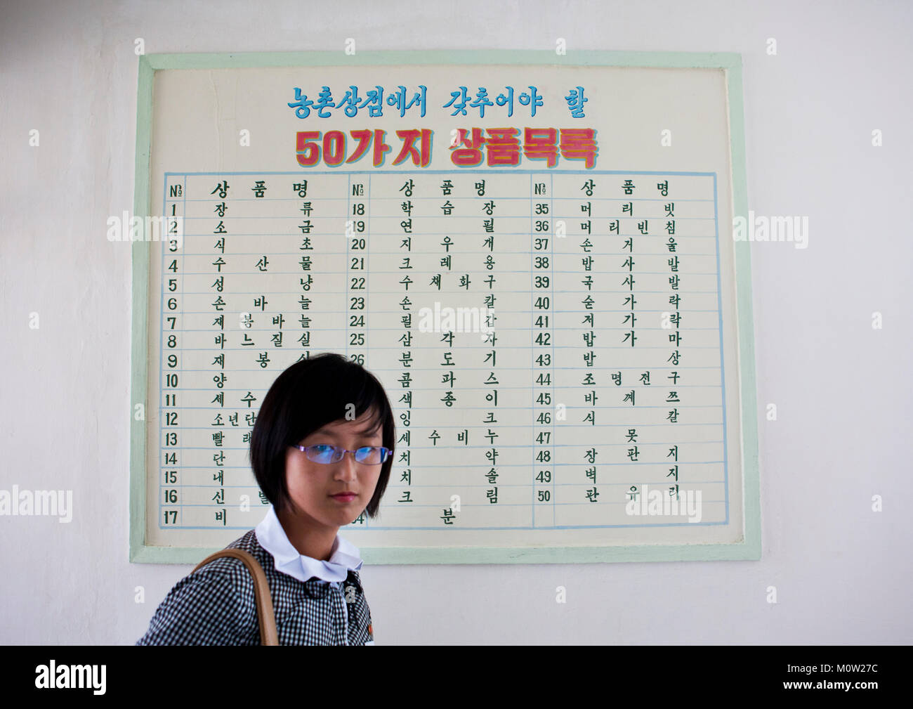North Korean woman in front of a list of products for sale in a small shop, South Hamgyong Province, Hamhung, North - Stock Image