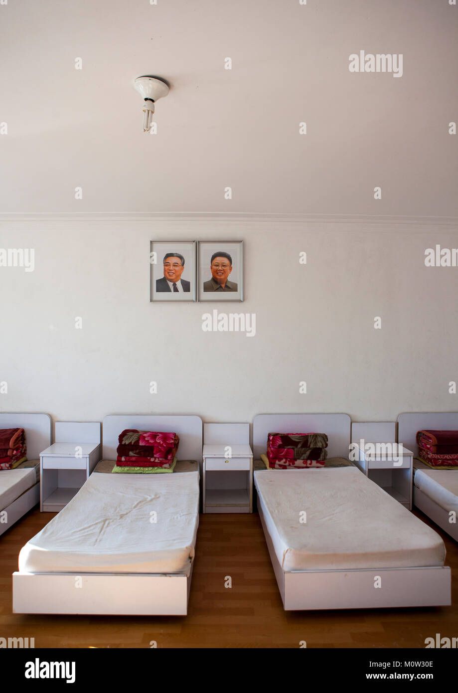 Bedroom with the official portraits of the Dear Leaders in Songdowon international children's camp, Kangwon - Stock Image