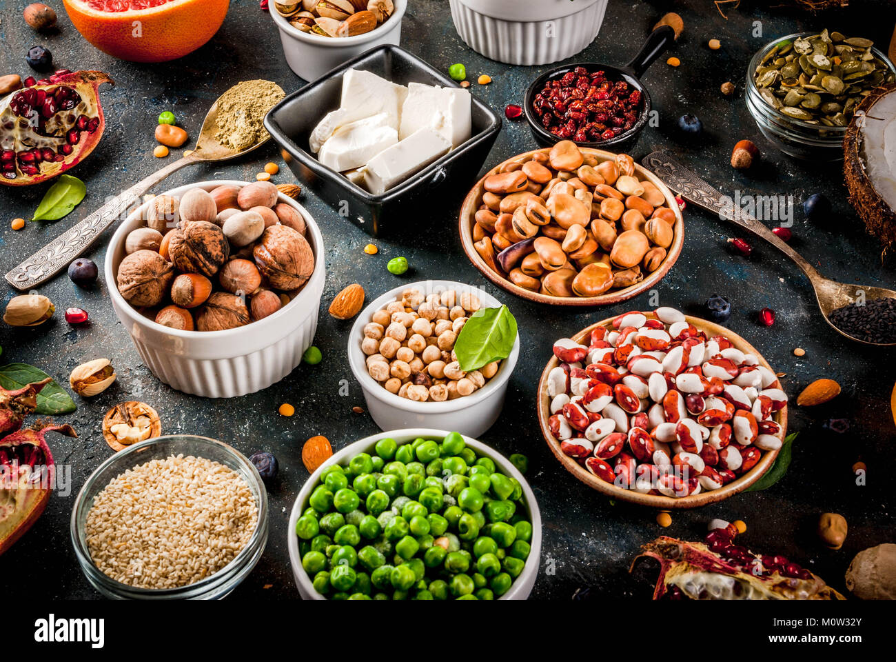 Set of organic healthy diet food, superfoods - beans, legumes, nuts, seeds, greens, fruit and vegetables. Dark blue Stock Photo