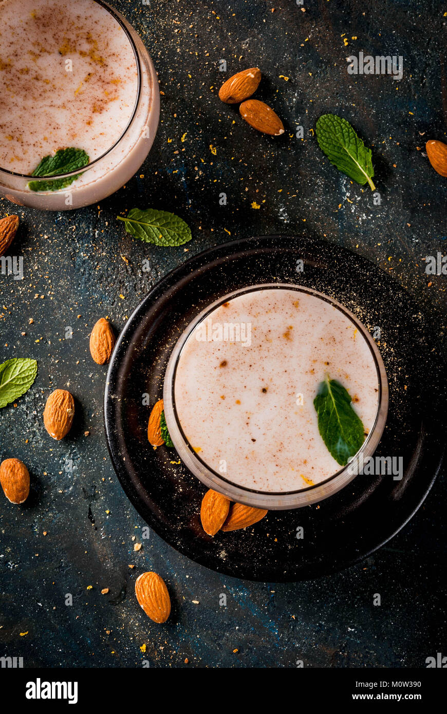 Traditional Indian beverage, Holi festival food, Thandai Sardai milk drink with nuts, spices, mint. Dark blue background, - Stock Image