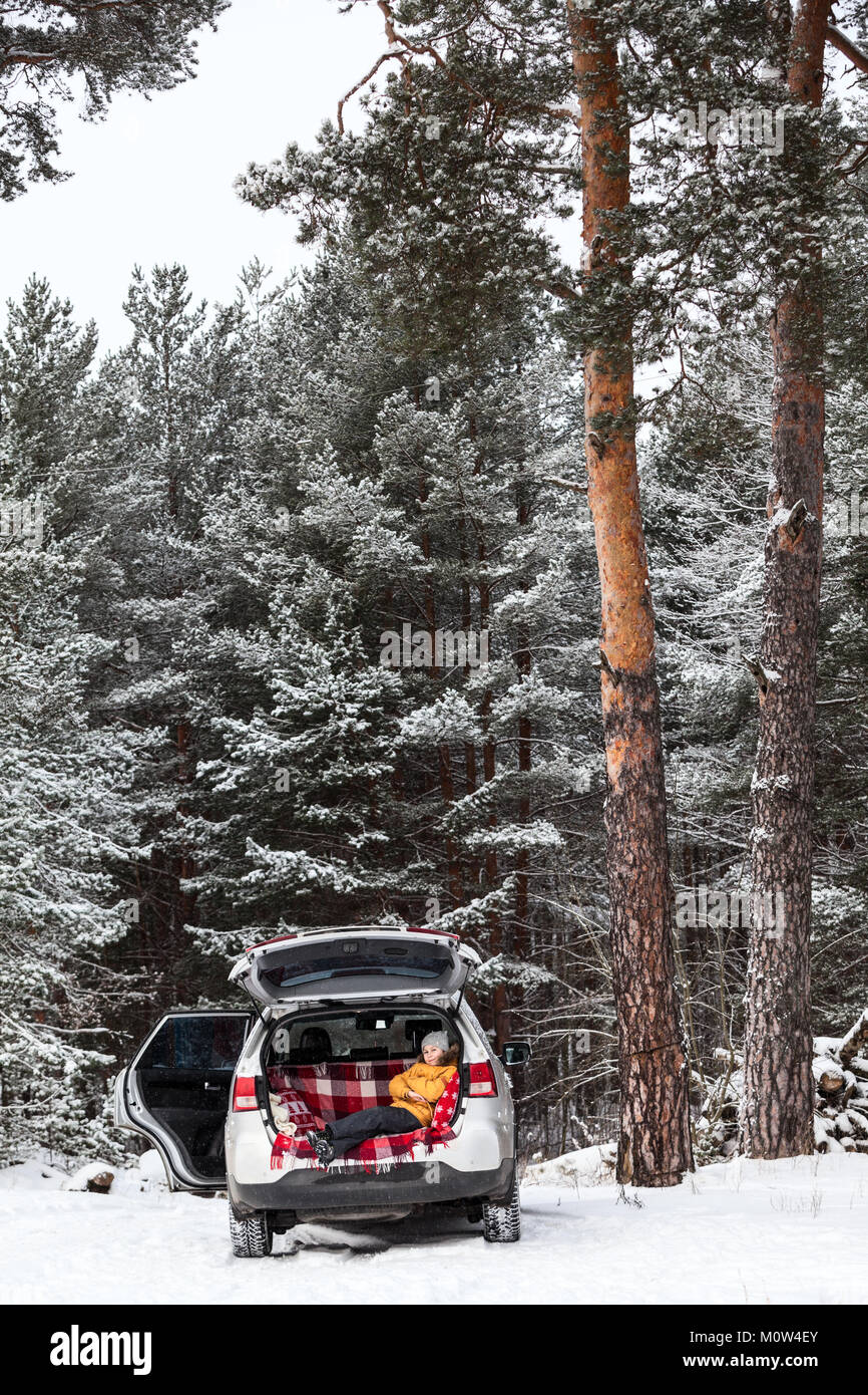 Child waiting parents in car trunk for luggage. Laying inside of vehicle with opened side and back doors. Winter - Stock Image