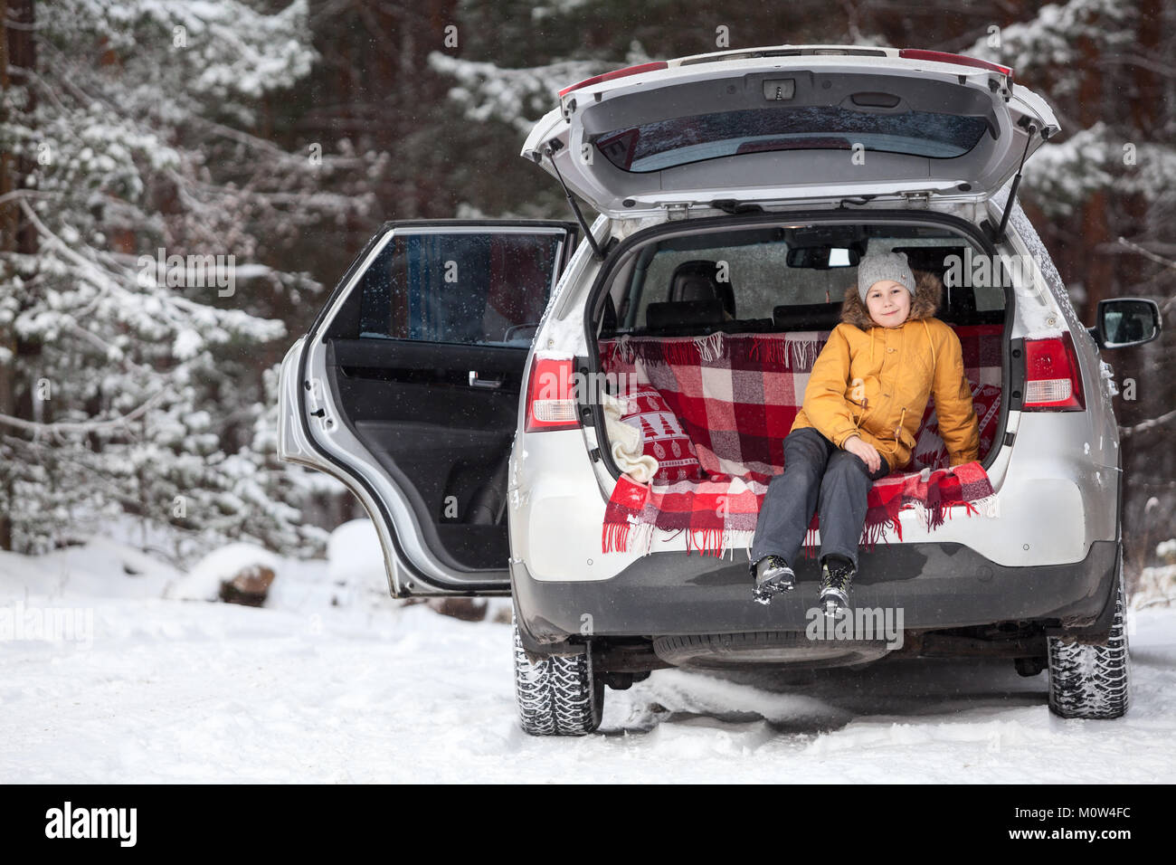 Happy child sitting inside of car trunk for luggage. Winter evergreen forest with huge snow covered pines. Copyspace - Stock Image