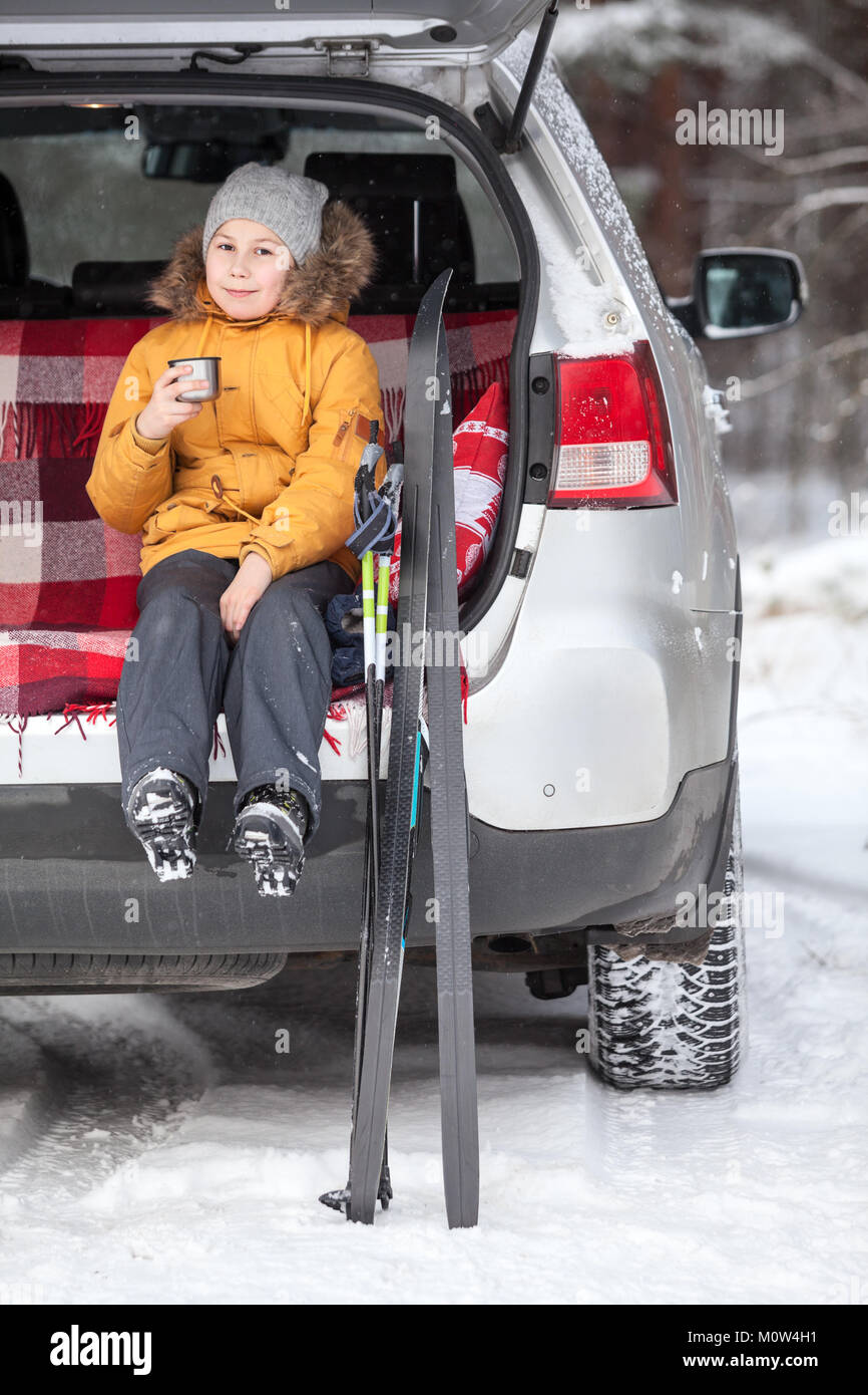 Young girl drinks hot tea after skiing while sitting in trunk of suv car. Winter activities - Stock Image